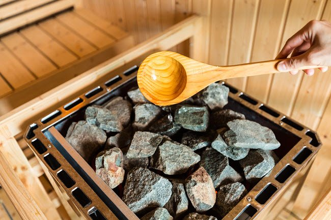A sauna generates intense heat from a traditional rock-laden stove.