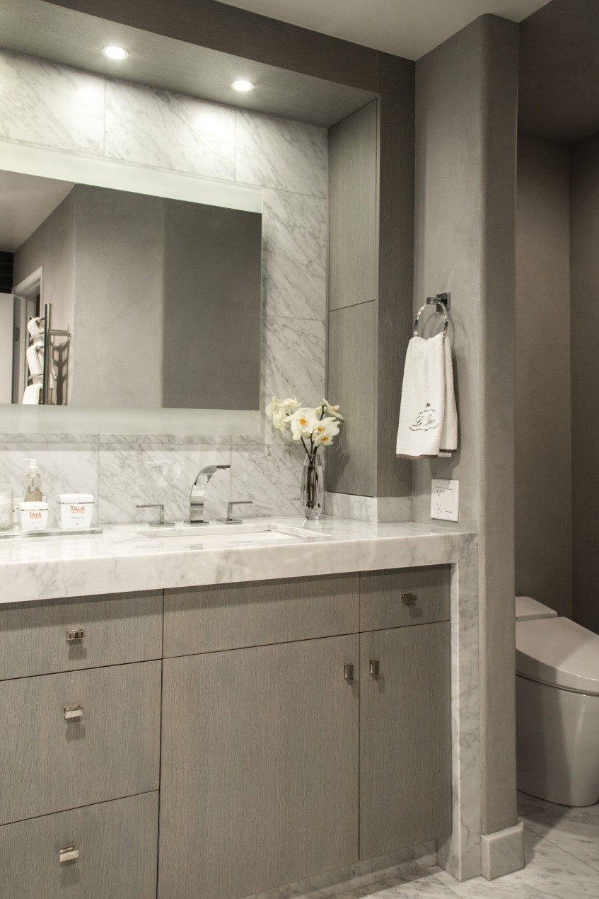 A rectangular mirror is flanked by two narrow counter-to-ceiling medicine cabinets