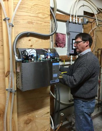 Ric Carpenter with Wolff Bros. Supply Inc. adjusts the wiring on a Mr.Steam generator.